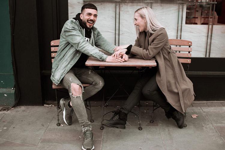foto smejuci sa par sediaci pri stole